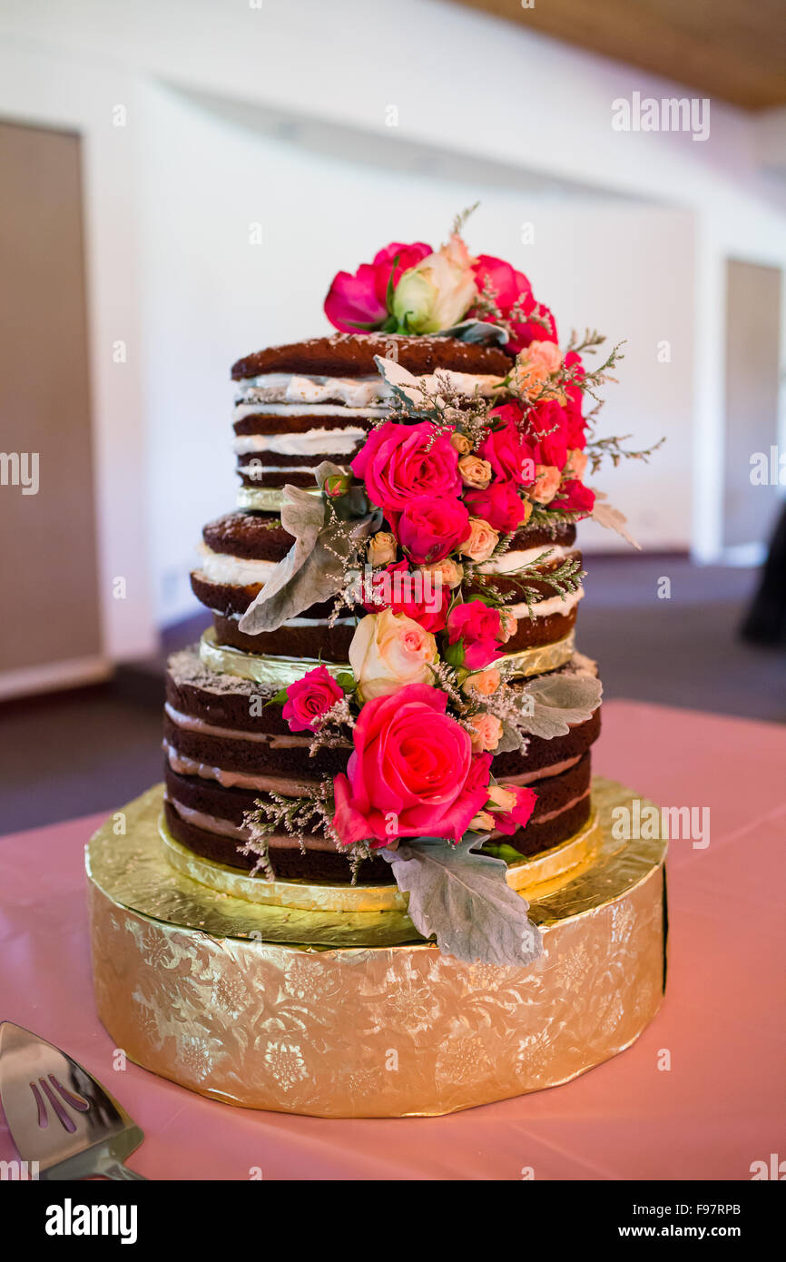 Custom wedding cake at reception with pink flowers and different ...