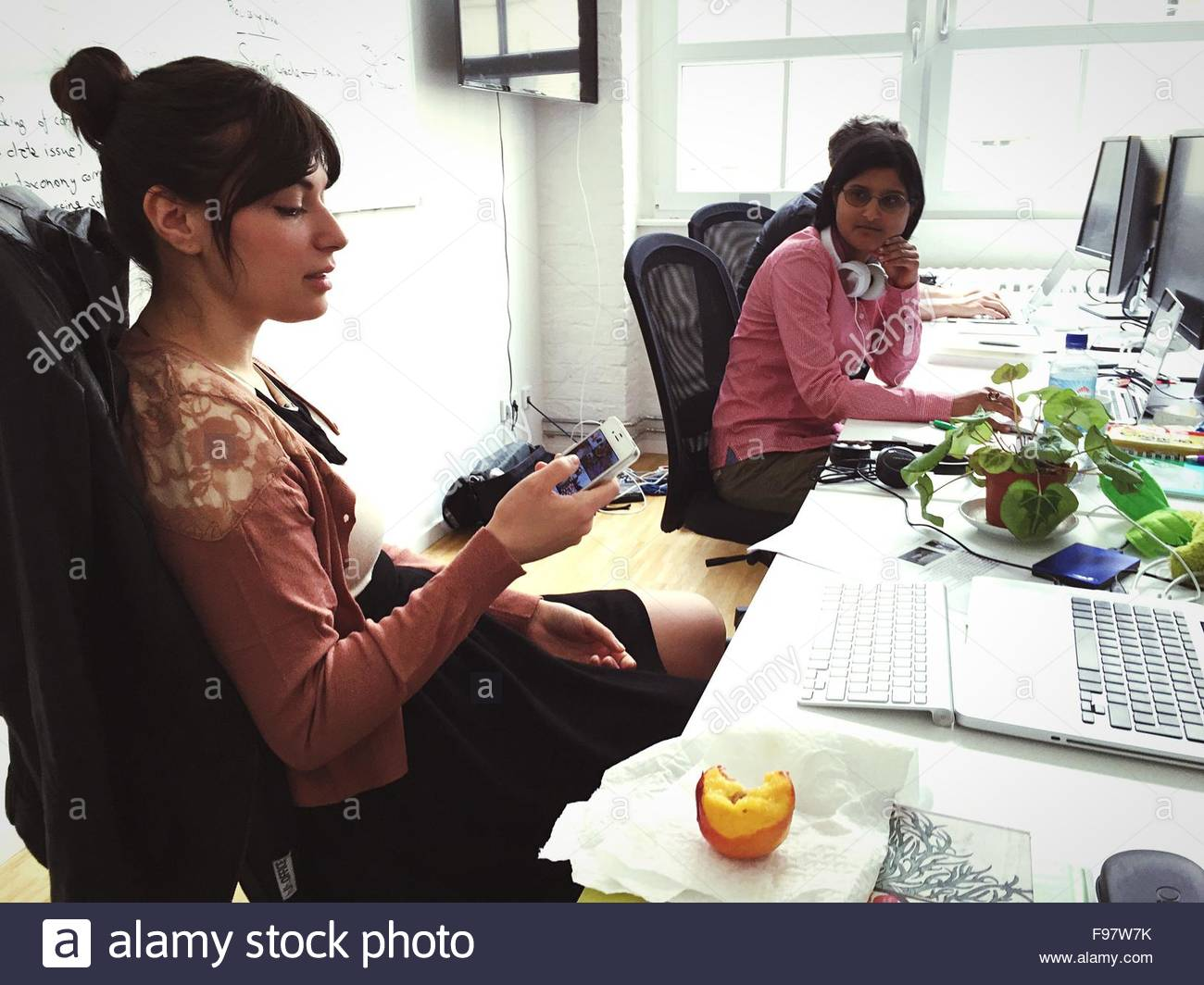 Beautiful Businesswoman Using Phone While Female Colleague Looking At Her In Office - Stock Image