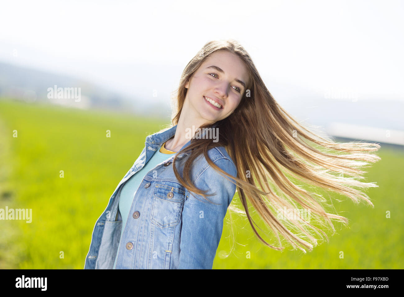 63cbf25dd2 Happy young girl in blue jeans jacket enjoying free time in green field -  Stock Image
