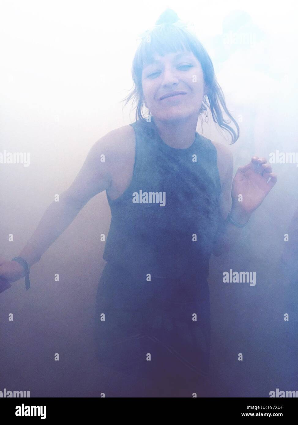 Portrait Of Happy Woman Dancing In Smoke - Stock Image