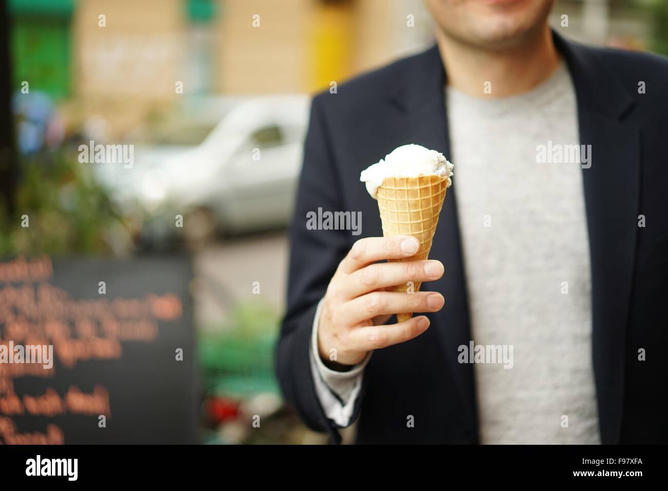 Midsection Of Man Holding Ice Cream On Street - Stock Image