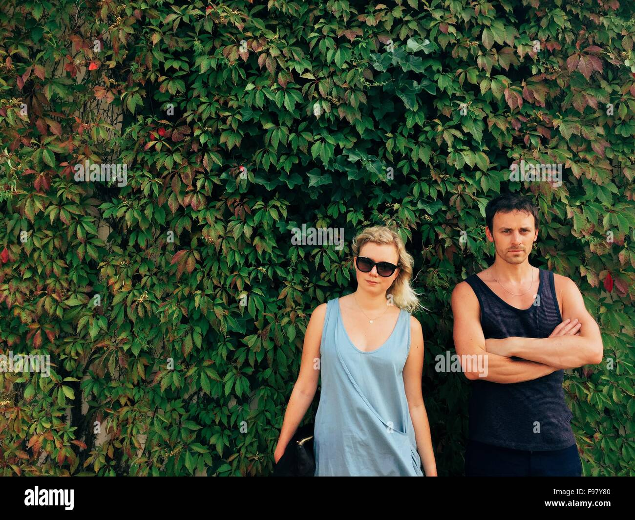 Portrait Of Friend Standing Against Ivy Covered Wall - Stock Image