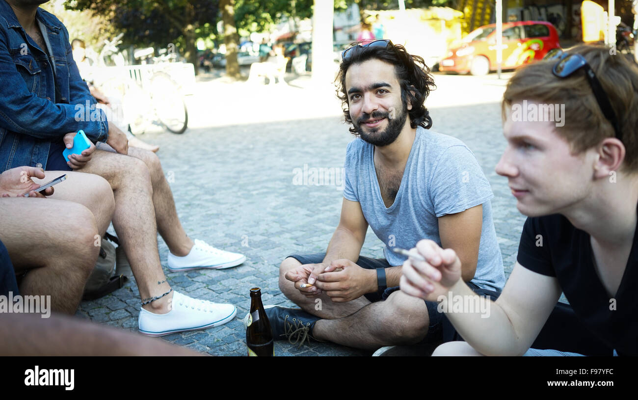 Friends Discussing While Sitting On Street - Stock Image