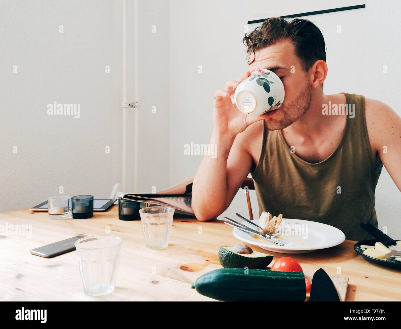 Man Drinking Coffee By Messy Table Stock Photo