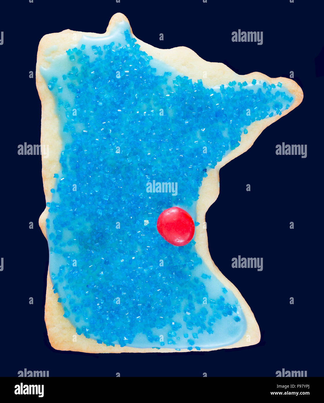 A holiday sugar cookie shaped like the US state of Minnesota with the red candy dot representing the Twin Cities - Stock Image