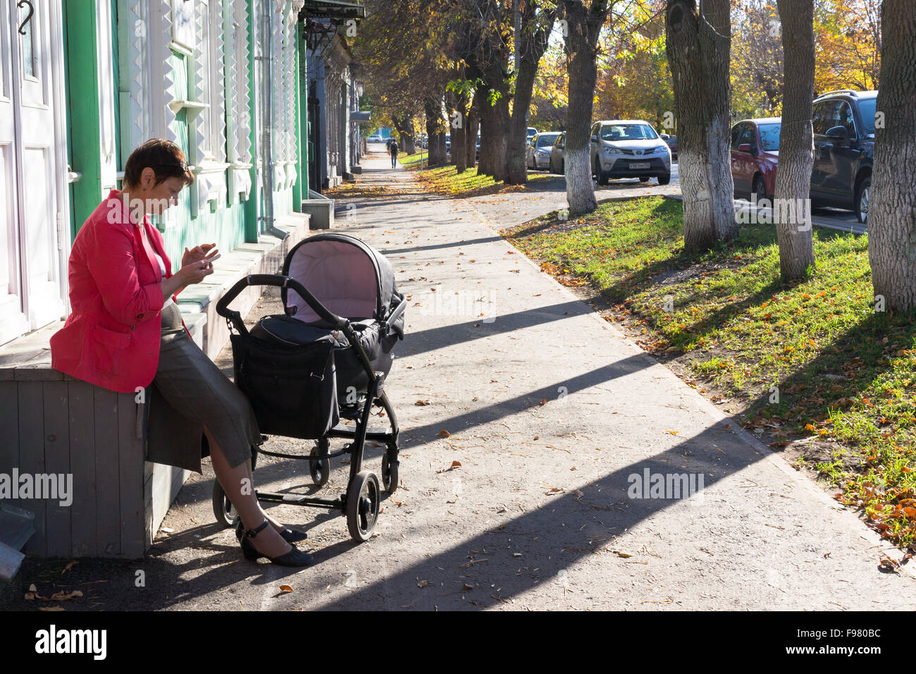 Woman with a baby in a pram sits on a wooden box and uses her mobile phone on an autumnal footpath in Ufa Russia - Stock Image