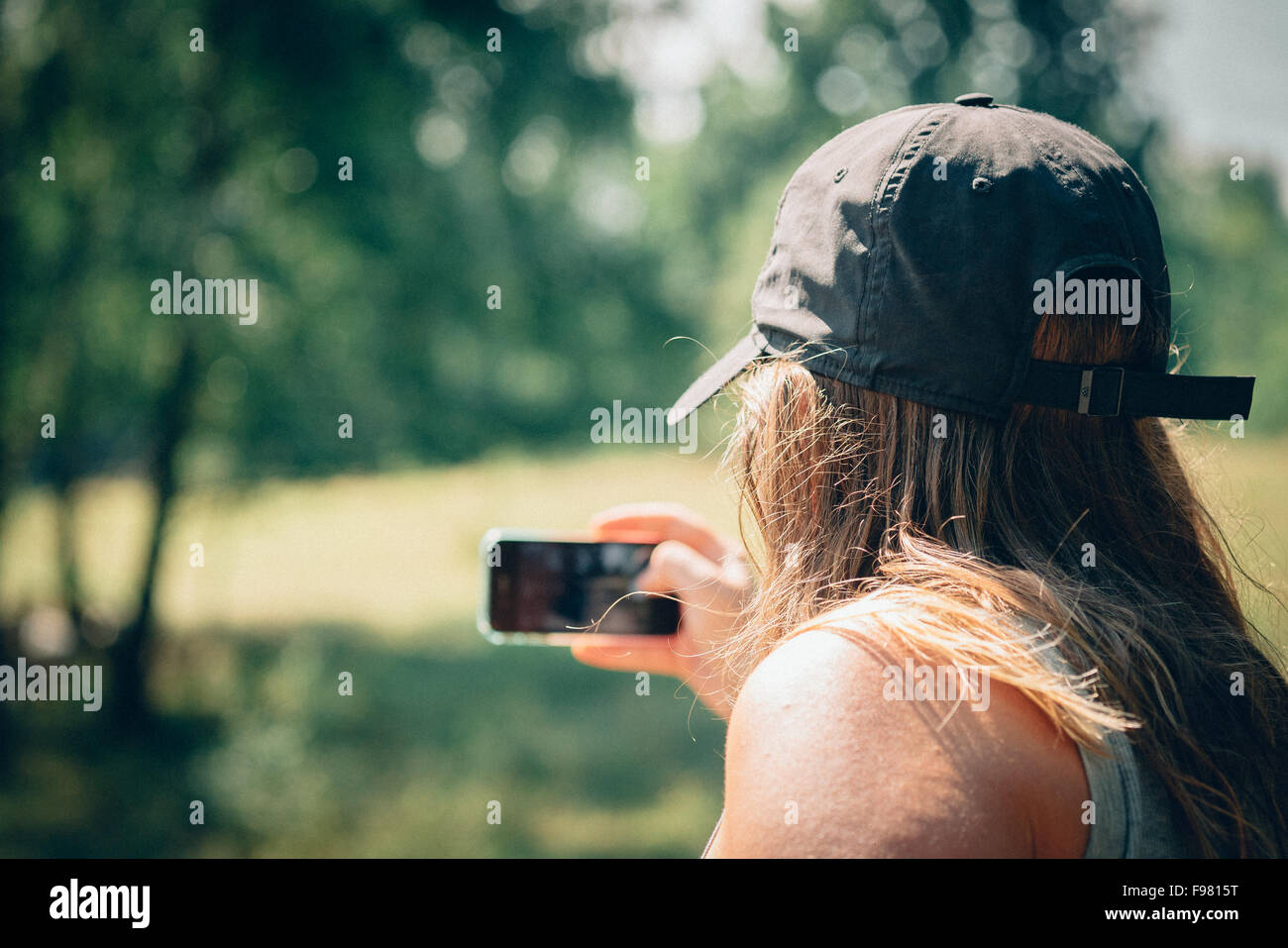 Rear View Of Man Clicking Selfie Outdoors - Stock Image