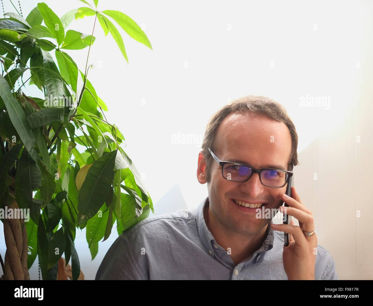 Portrait Of Happy Man Listening To Mobile Phone By Plant Against Wall - Stock Image