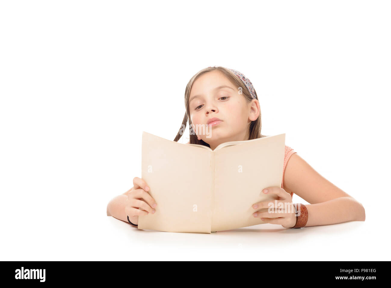 a little student girl studying and reading book at school - Stock Image