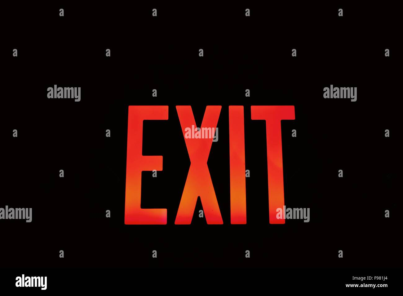 Red Exit Sign Against Black Background - Stock Image