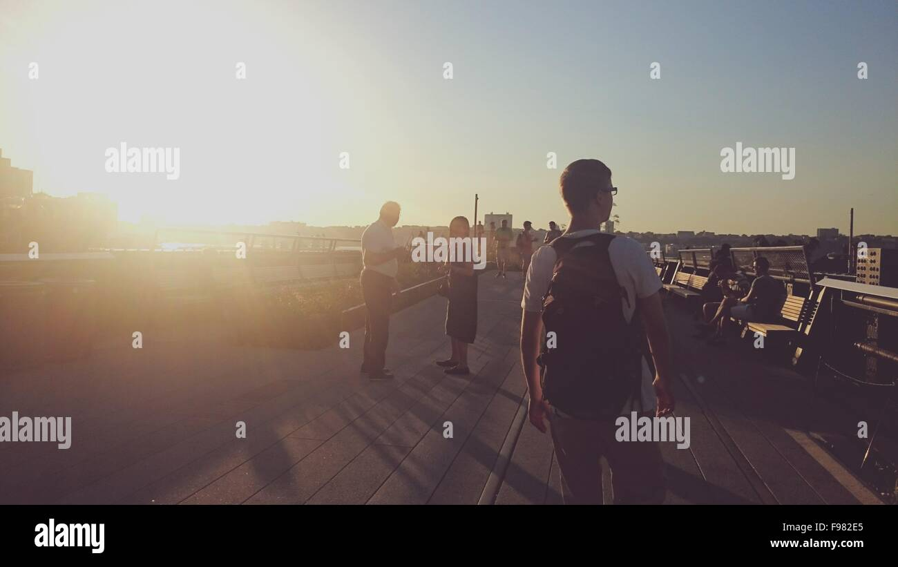 Rear View Of Man With Backpack Walking On Street Against Clear Sky At Sunset - Stock Image