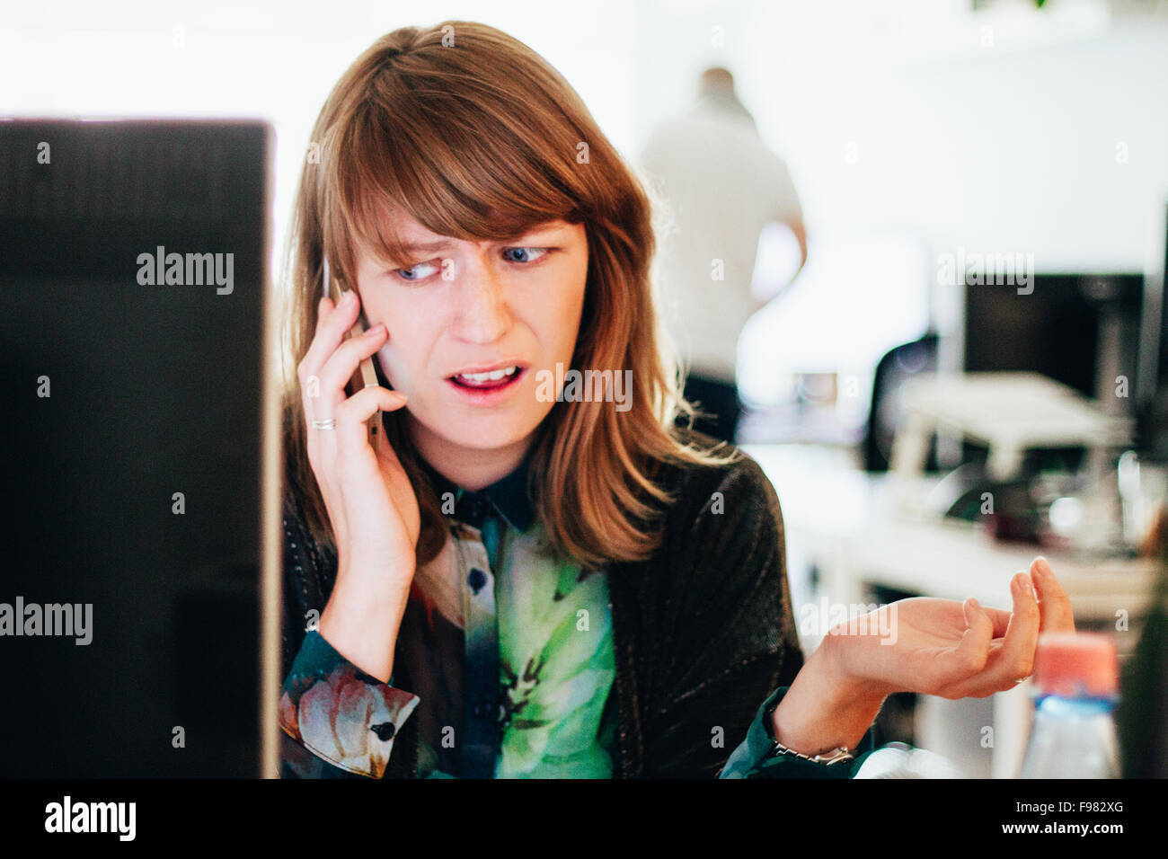 Worried Woman Talking On Mobile Phone While Sitting At Computer Desk In Office - Stock Image