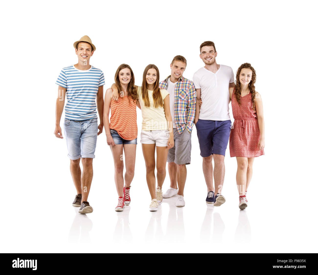 Group of happy young people walking, isolated on white background. Best friends - Stock Image