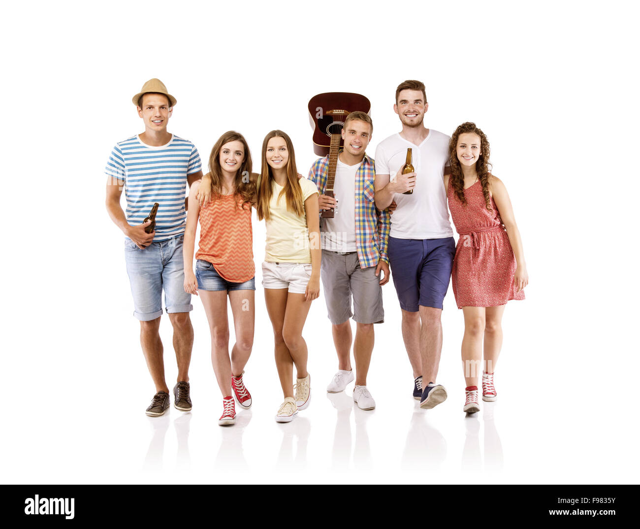 Group of happy young people walking, taking guitar and drinks with them, isolated on white background. Best friends - Stock Image