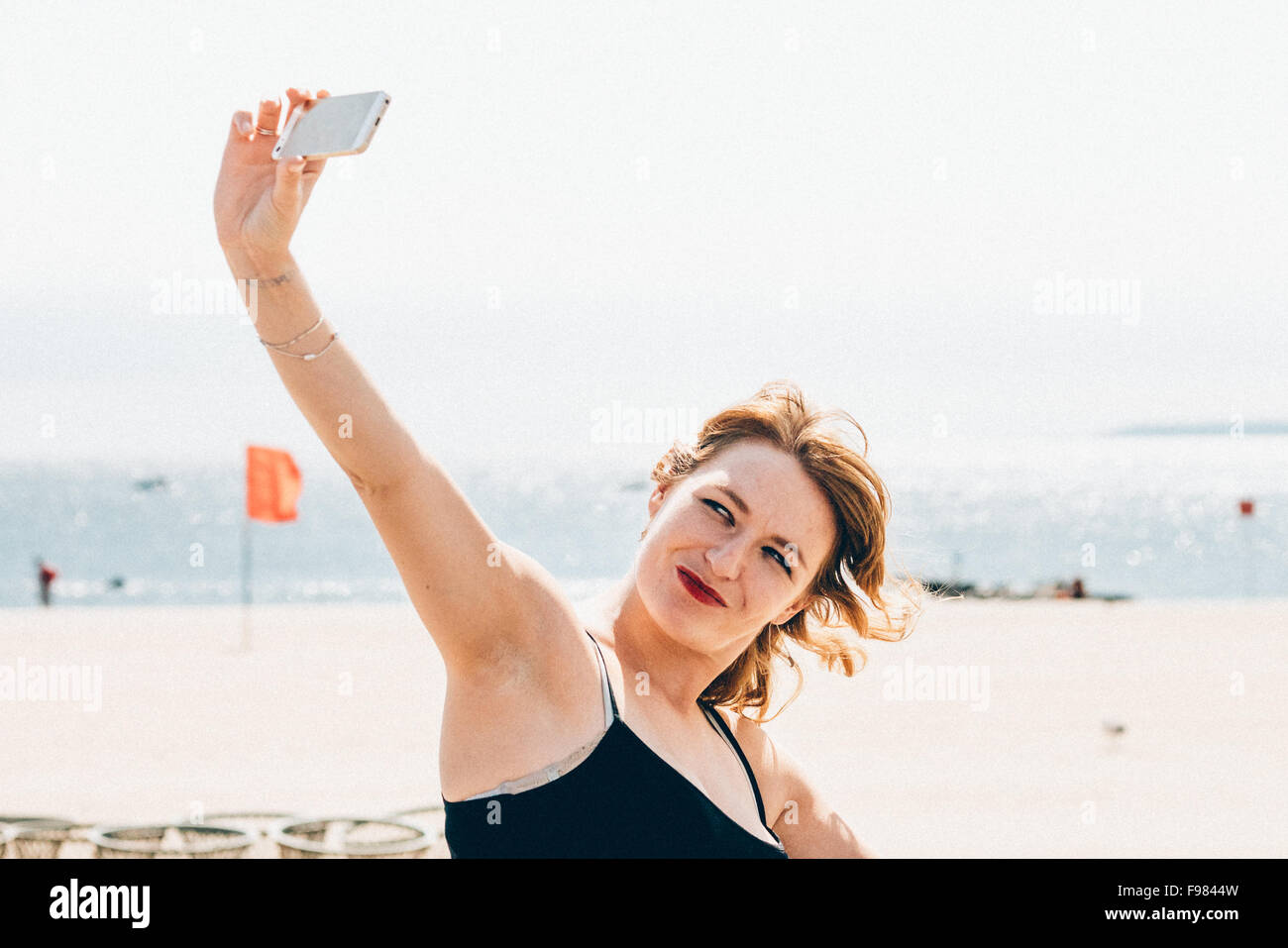 Young Woman Clicking Selfie On Smart Phone While Standing At Shore - Stock Image