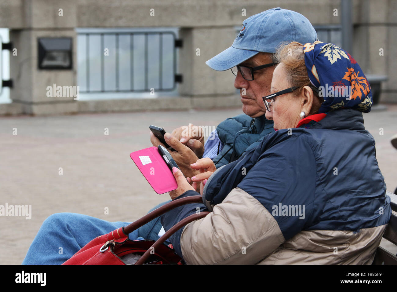 Seniors couple at Canadian Falls and checking their cell phones. Horseshoe Falls. View from Niagara Falls, Ontario, - Stock Image