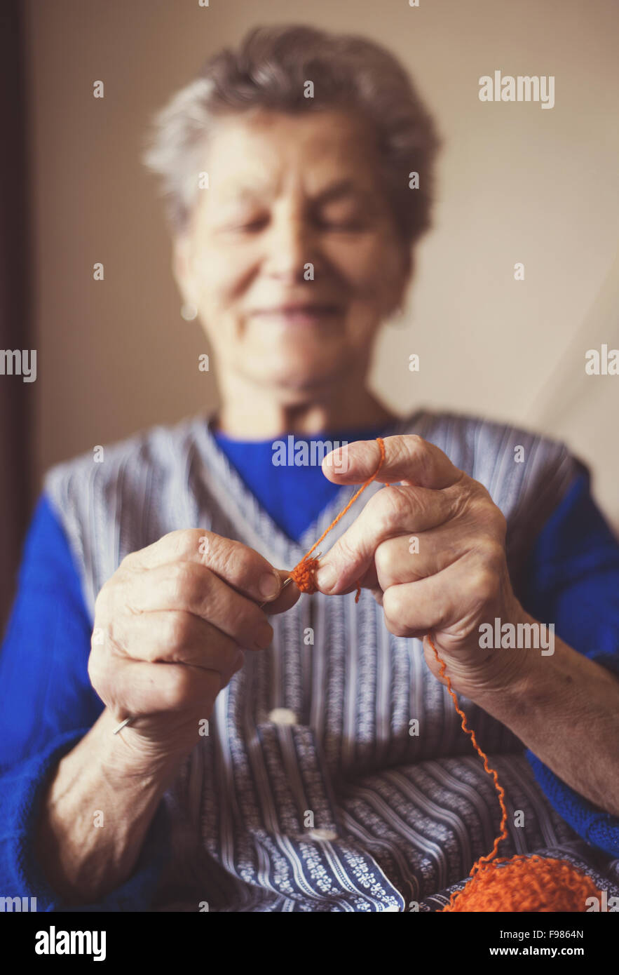 Portrait of senior woman sitting in armchair and knitting at home - Stock Image