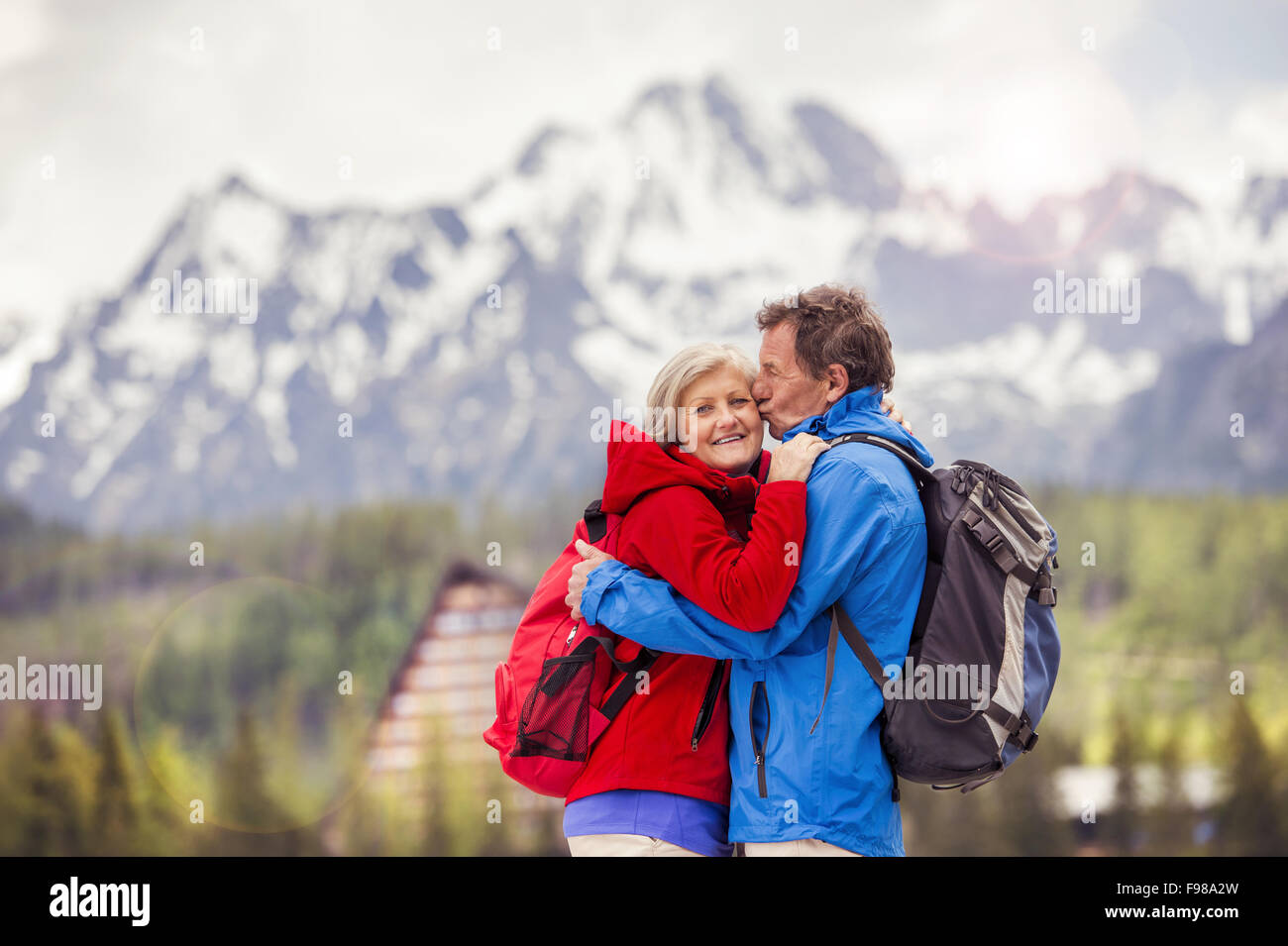 Senior hikers couple kissing during the walk in beautiful mountains, hills and hotel in background - Stock Image