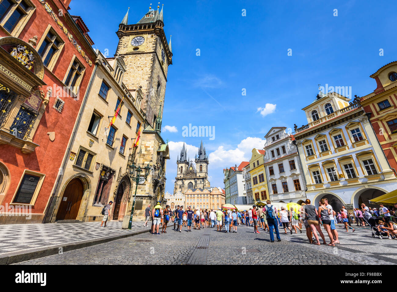 Tourists in Stare Mesto Square with Old Town Tower and Tyn Church, main attraction of Prague, Bohemia. - Stock Image