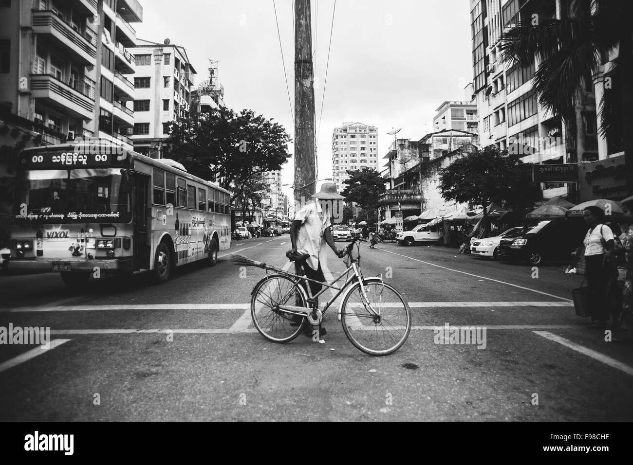 a man pushes his bicycle across a busy street in yangon - Stock Image