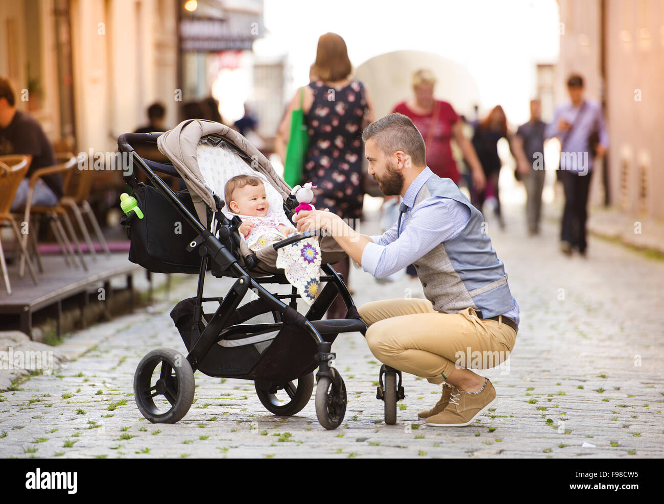 2815548ed Handsome hipster modern businessman with beard walking with baby in pram in  town - Stock Image