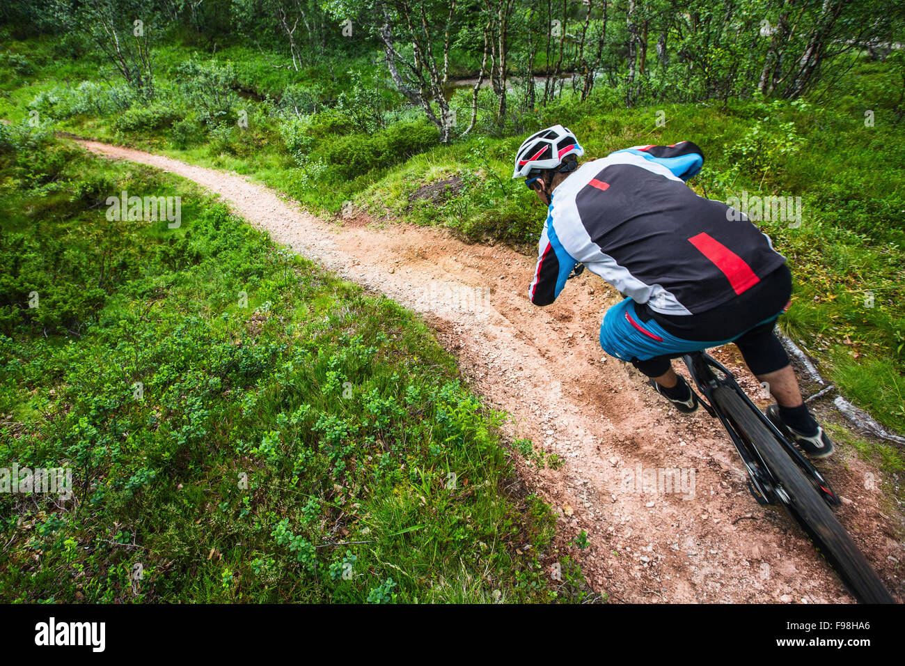 Mountain biker in a fast paced corner in Valadalen, Sweden. - Stock Image