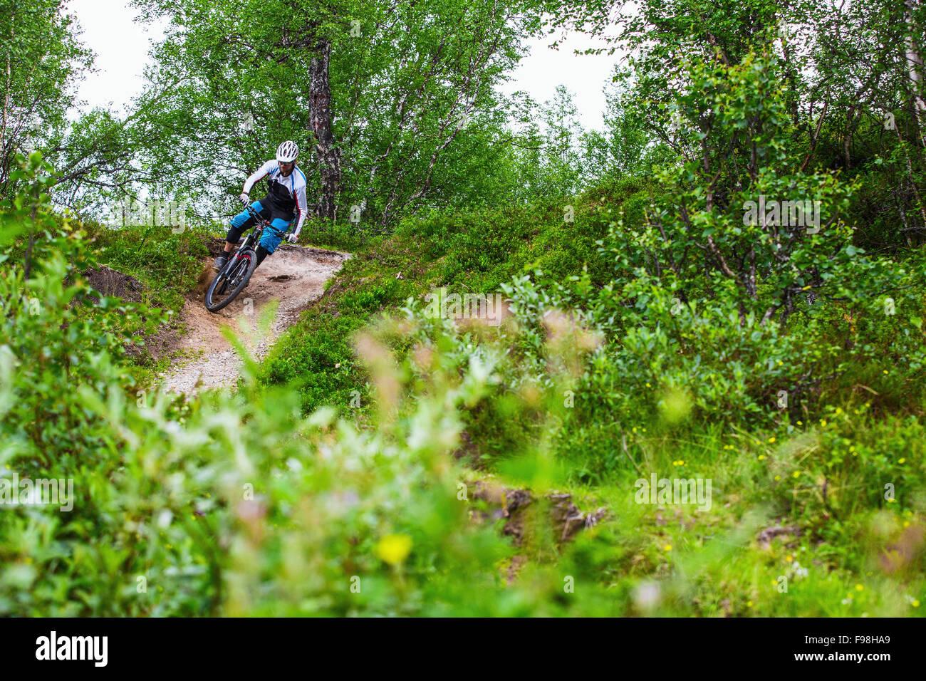 Mountain biker tackles a corner in Valadalen, Sweden. - Stock Image