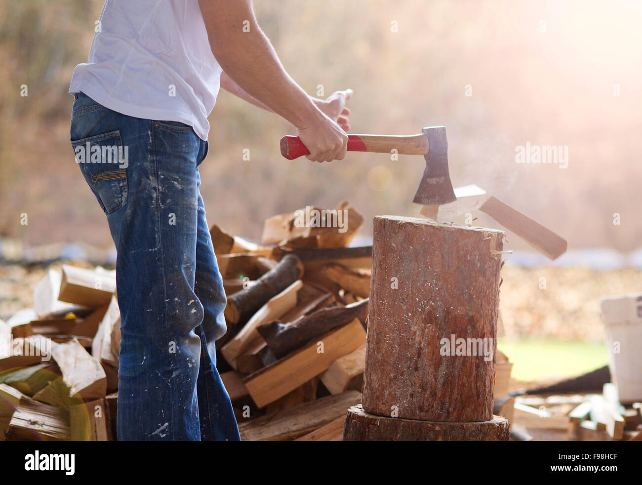 Detail of young man chopping wood in his backyard - Stock Image