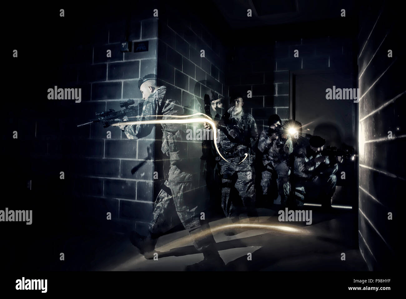 In pitch darkness, Air Force Security Forces members tactically move through a building using only the flashlights - Stock Image