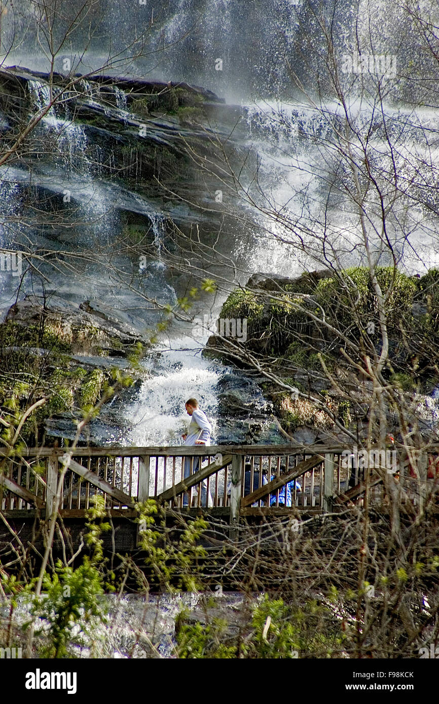 A hiker crosses a bridge with Amicalola Falls in the background at Amicalola Falls State Park in North Georgia. - Stock Image