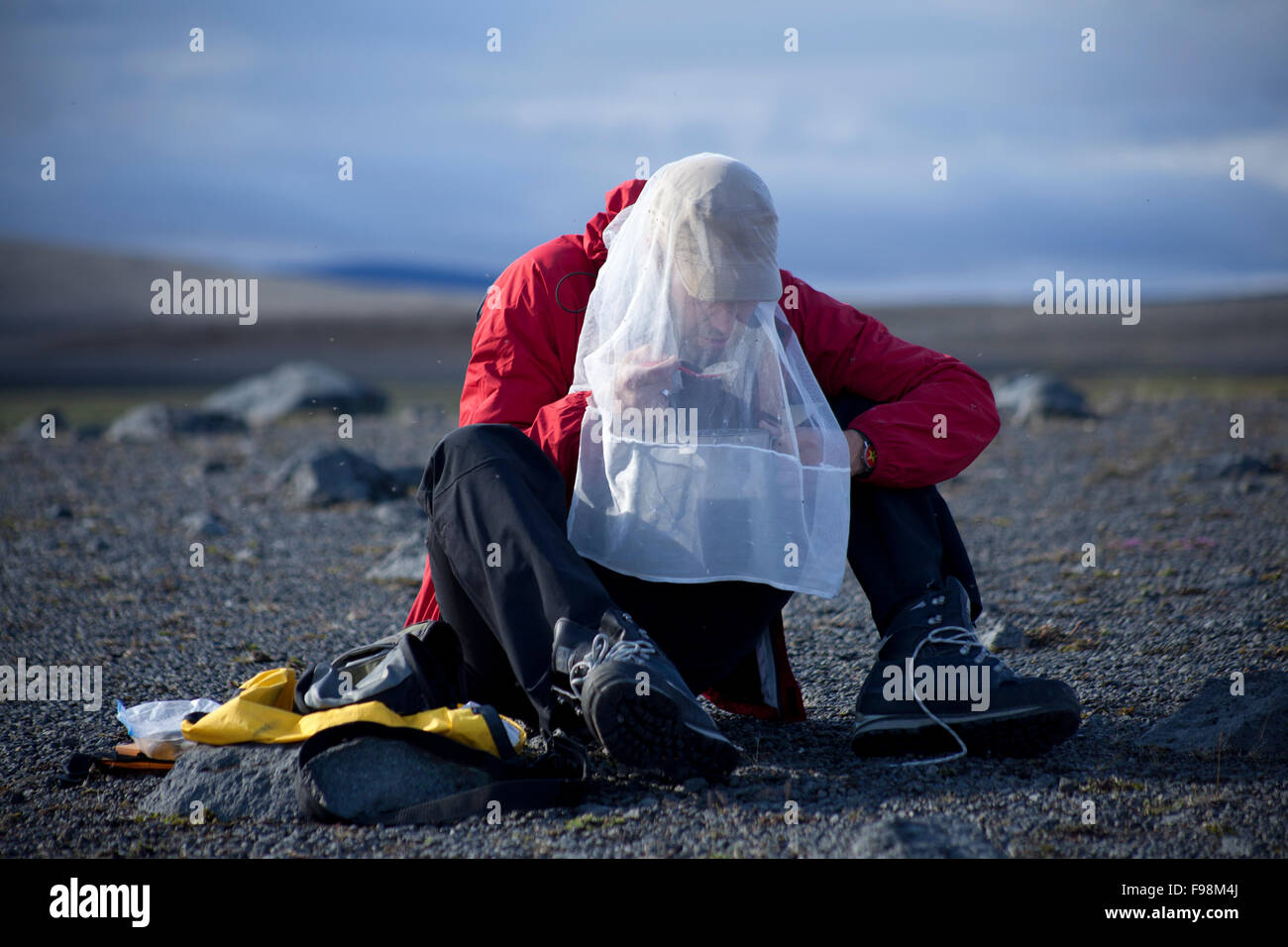 Young man eating breakfeast while camping - Stock Image