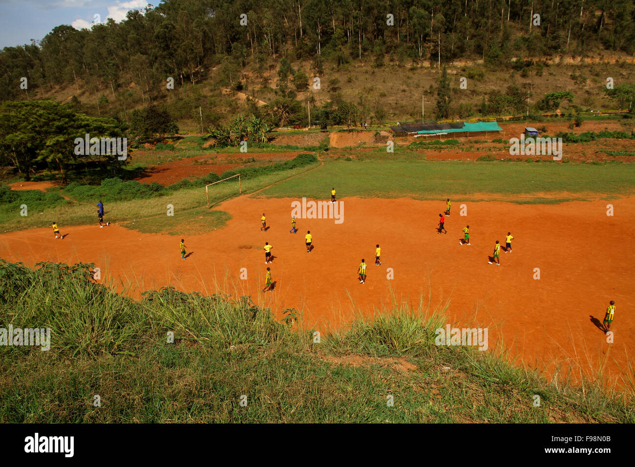 A group of African children, in Rwanda, Kigali, play soccer on a dirt field - Stock Image