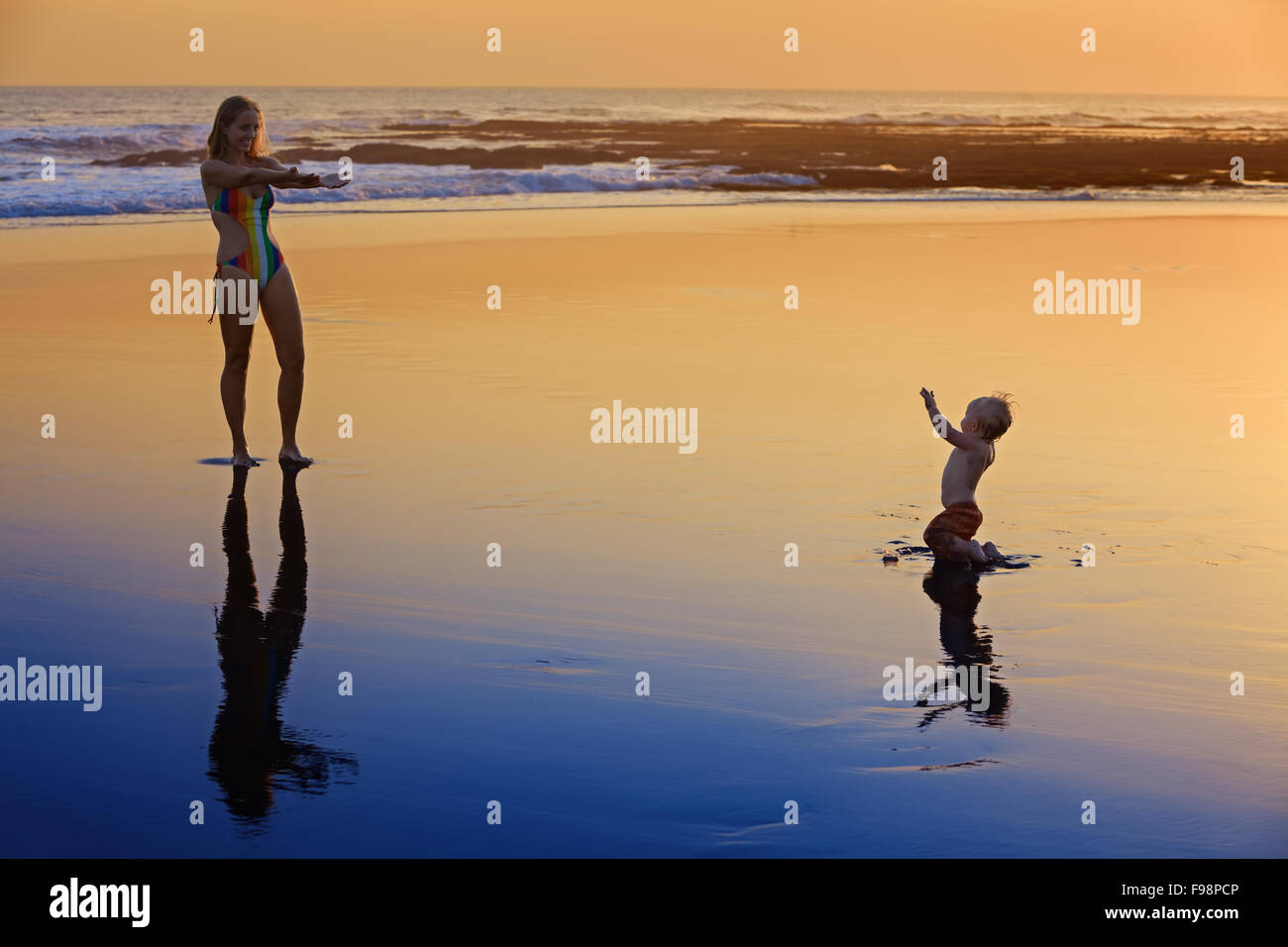 Silhouette with black shadows of mother with baby running on wet gold sunset sand to sea surf to swim in beach wave. - Stock Image