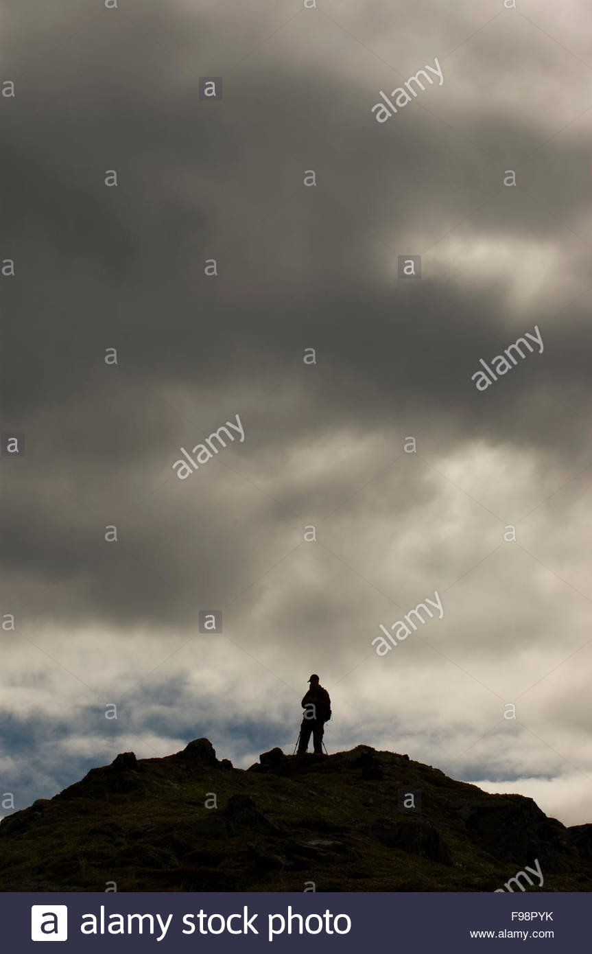 A hiker pauses to admire the view of an unnamed valley on Unalaska Island, Alaska. - Stock Image