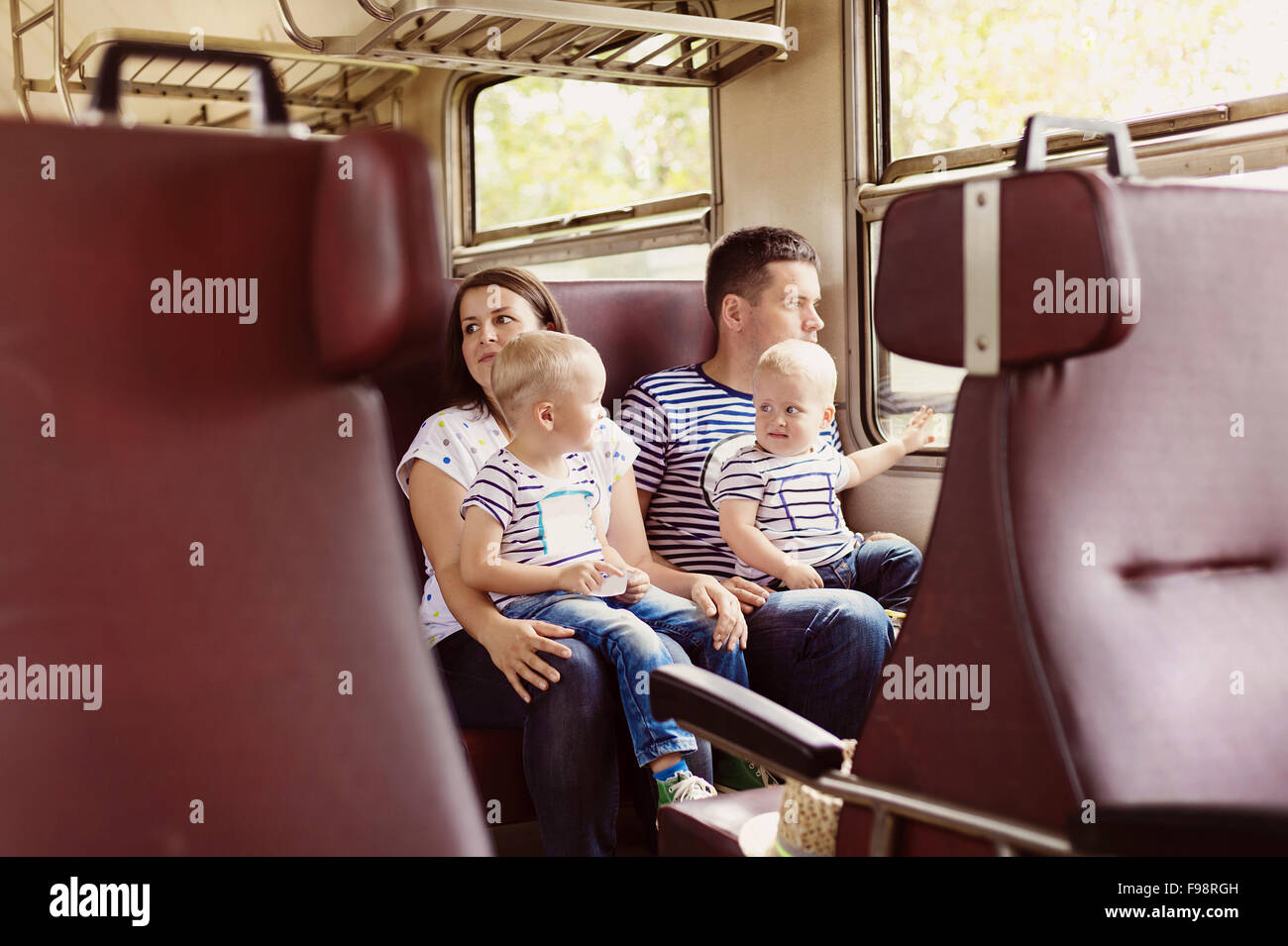 Family with two children travel in retro train. - Stock Image