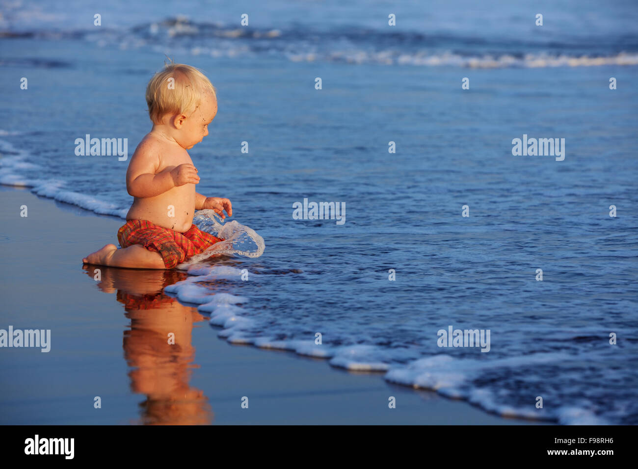 On sunset beach happy baby swimmer sit on black sand and look at sea surf with foam and splash for swimming in waves. Stock Photo