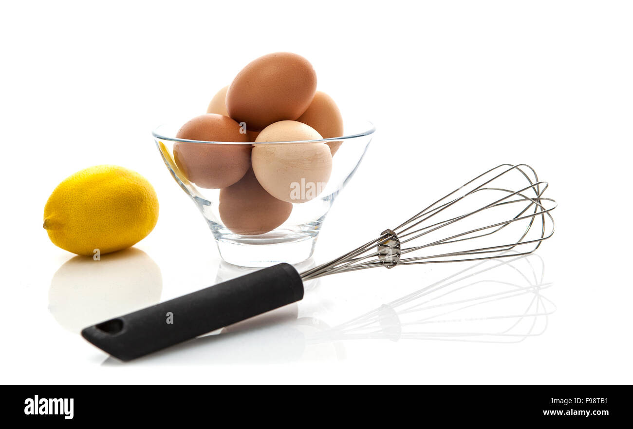 Metal whisk with fresh eggs and lemon on a white background - Stock Image
