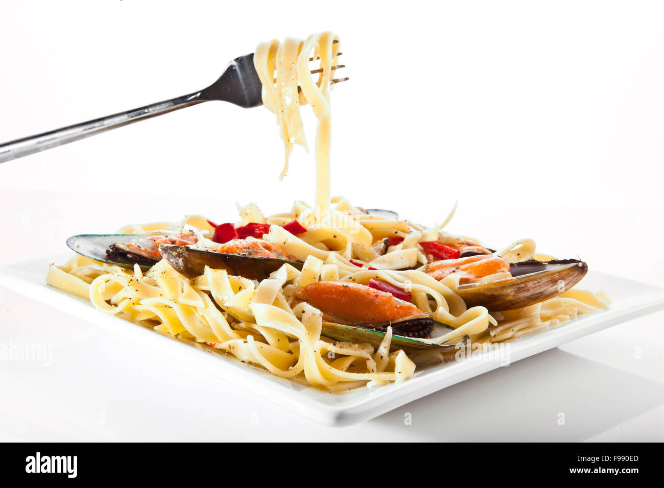 Pasta with mussels on white dish - Italian food - Stock Image