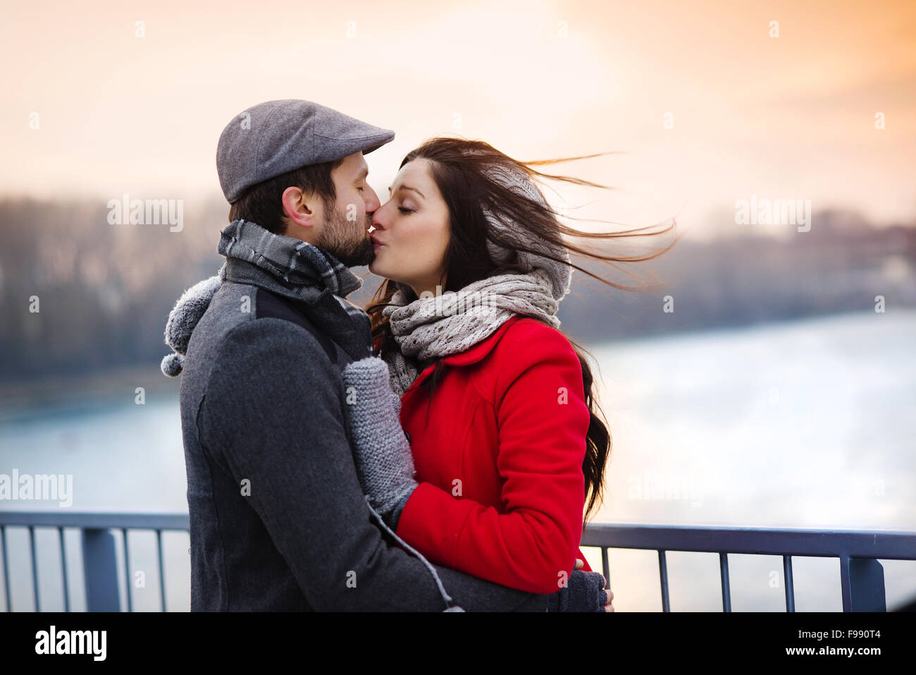 Young couple kissing by the river in winter weather - Stock Image