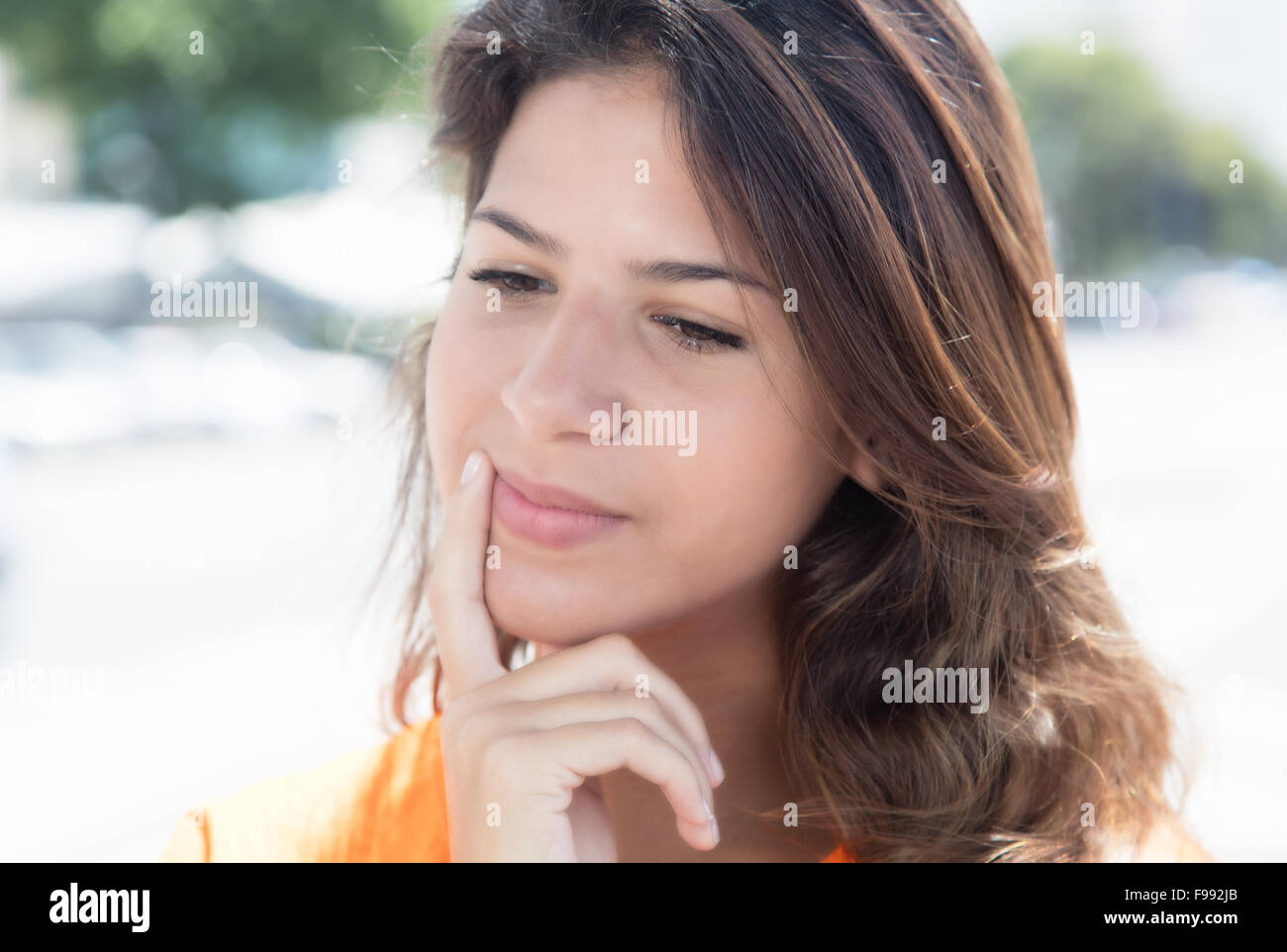 Thinking caucasian woman in a orange shirt with buildings and street in the background Stock Photo