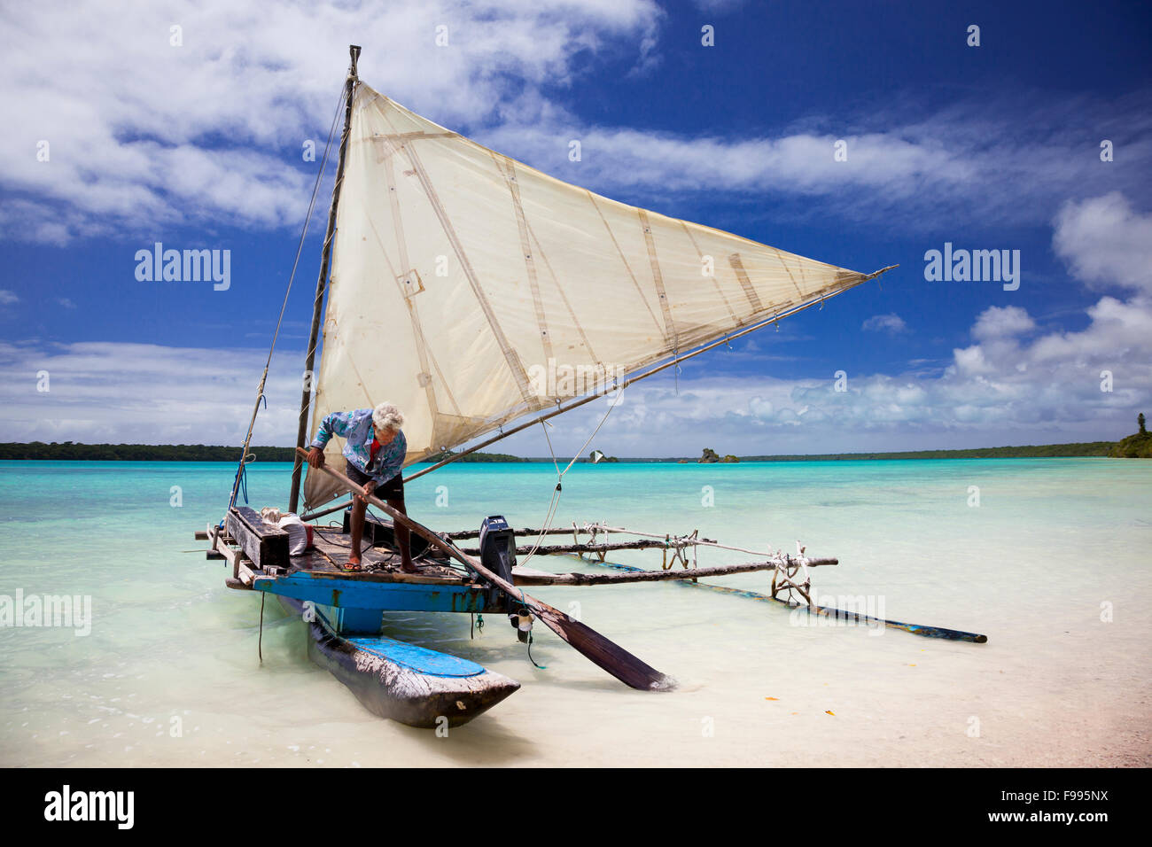 Theodore, a local 'kunie,' prepares a traditional outrigger canoe for sail across the spectacular Upi Bay - Stock Image