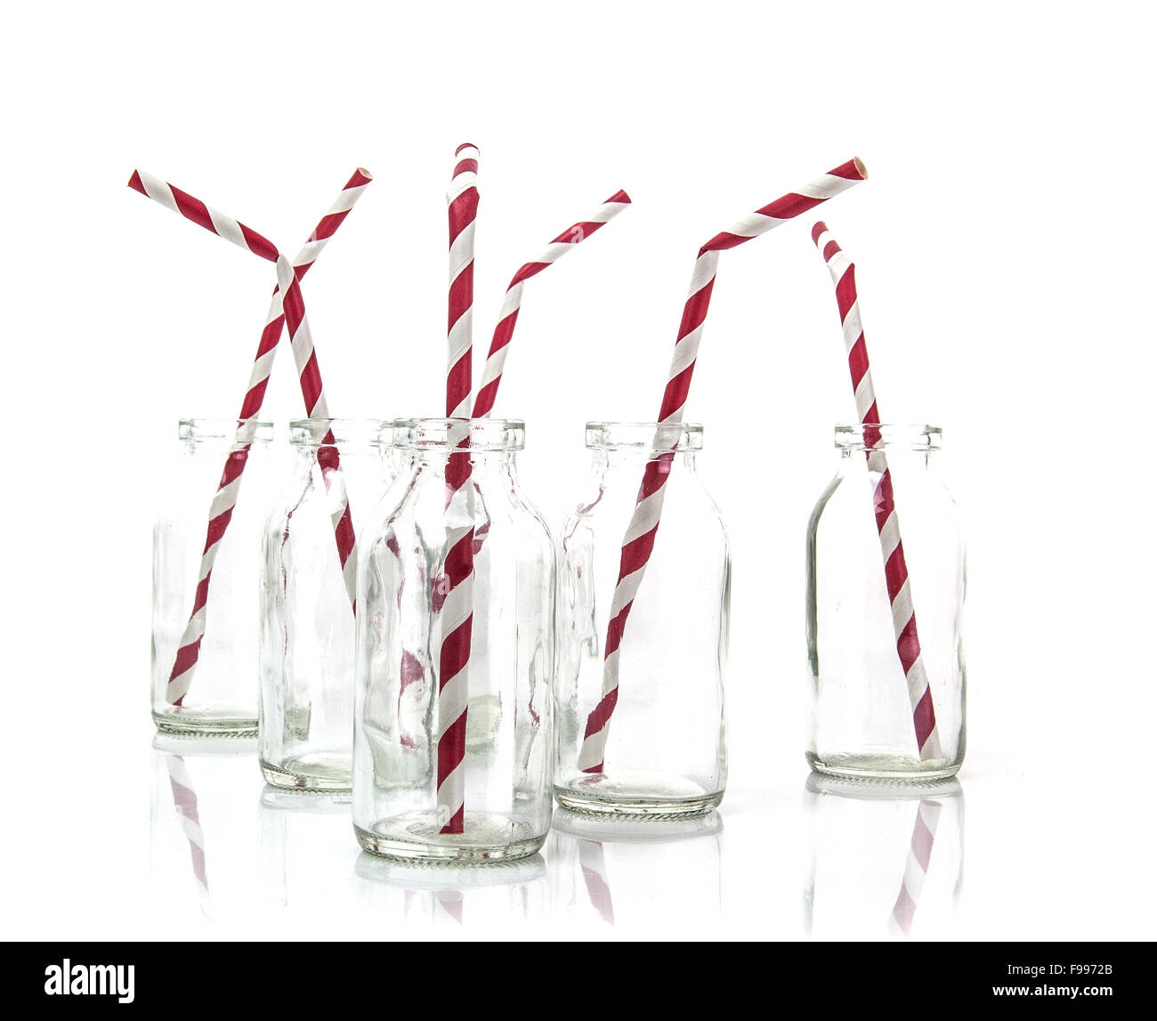 Six empty bottles of milk with drinking straws in a line on a white background Stock Photo