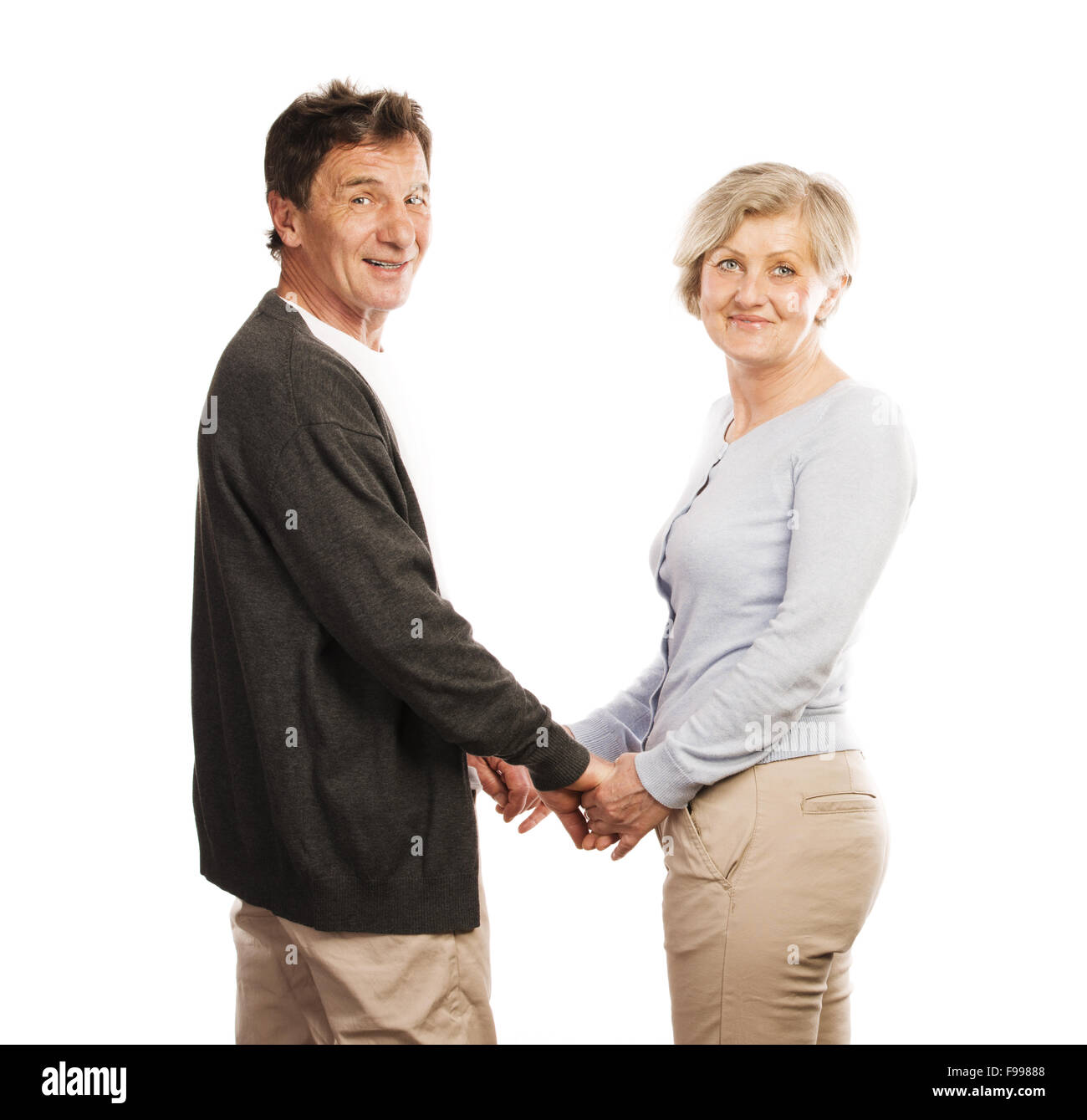Studio portrait of happy seniors couple holding hands. Isolated on white background. - Stock Image