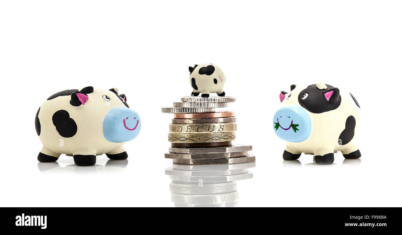 Small Beginnings - Small  Piggy Bank on top of coins with two larger ones looking up on white background - Stock Image