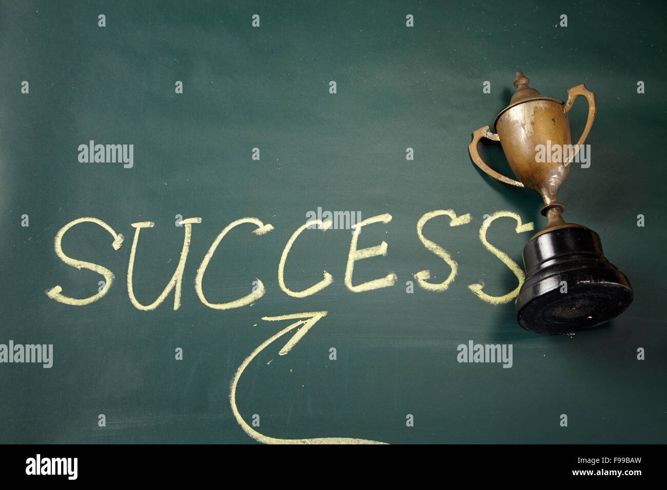 hand writting success and trophy on the blackboard - Stock Image