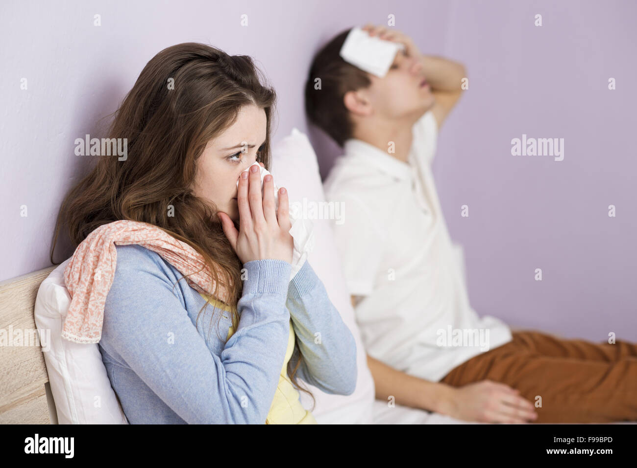 Sick woman and man have cold, flu and high fever. - Stock Image