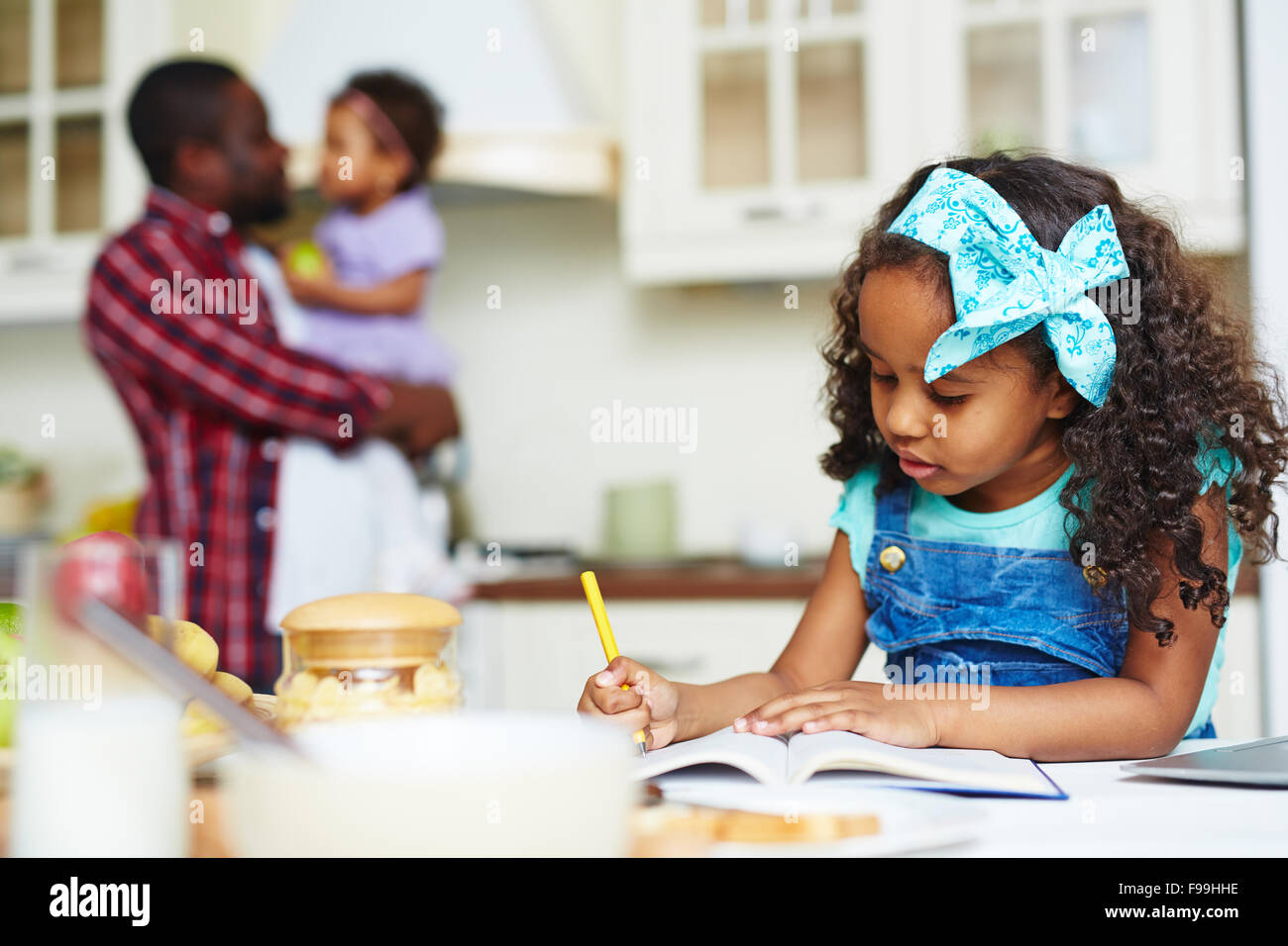 Cute schoolgirl making notes in exercise-book at home - Stock Image