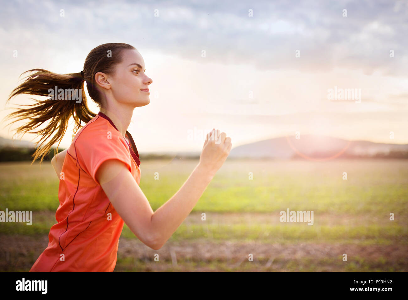 Cross-country trail running woman at sunset. Runnerwoman exercising outside as part of healthy lifestyle. - Stock Image