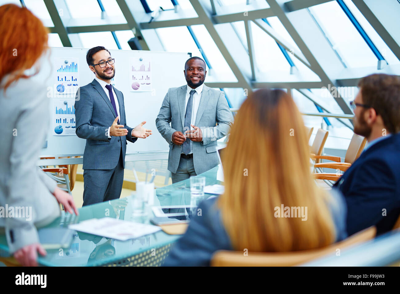 Two businessmen explaining colleagues latest data - Stock Image