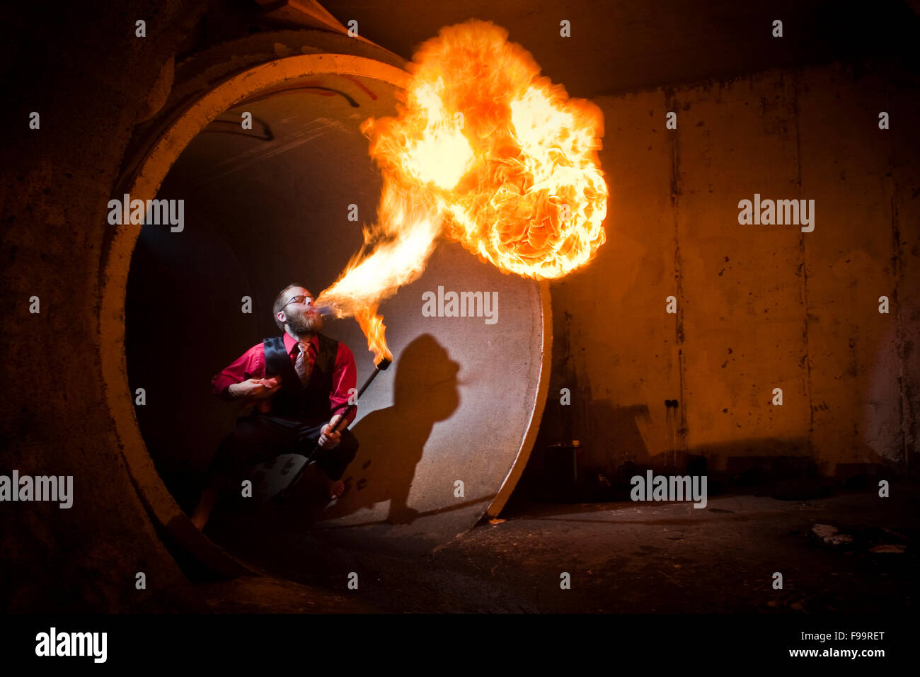 Fire breather blows flame in tunnel. - Stock Image